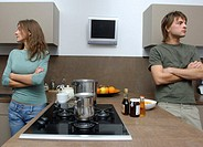 Young couple in kitchen, looking away from each other, arms crossed