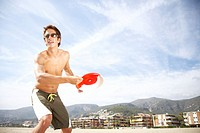 Young man on beach preparing to throw flying disc, smiling