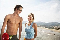 Young couple on beach, smiling, man holding flying disc