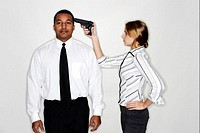 Businesswoman pointing a gun at her subordinate's head