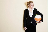 Businesswoman holding a ball.