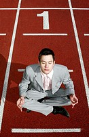 Businessman meditating on a running track (thumbnail)