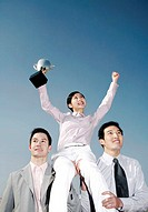 Businessmen lifting up a female winner