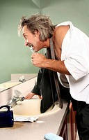 Businessman brushing teeth in the toilet.