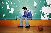 Businessman using laptop in a basketball court