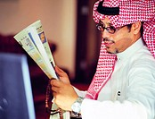Saudi businessman reading Arabic newspaper and holding prayer beads