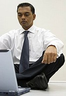Businessman sitting on top of a table with a laptop