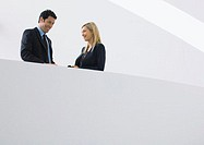 Businessman and woman standing together, smiling