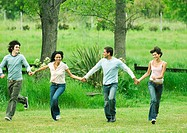 Four young friends holding hands and skipping in field
