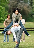 Young woman playing leapfrog with young man while friends look on