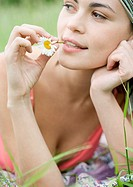 Young woman with flower stem in mouth