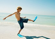 Boy wearing flippers on beach, taking big steps