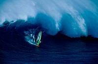 A windsurfer riding a big wave