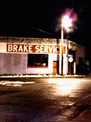 An automobile brake service shop in Albany, New York is captured at night with a slight blur
