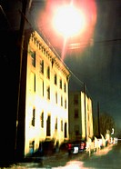 A desolute street in an industrail Upstate town is captured at night with a blurred, painterly effect