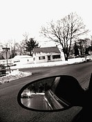 A surburban street scene in winter is captured in black and white, partially through  rearview mirroe