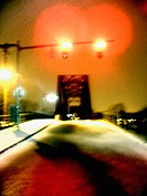 A train trestle is captured at night during the winter with fresh fallen snow.  Ghostly and mysterious