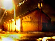 A warehouse on a desolute street corner is captured at night with a slight blur creating a mysterious, painterly effect