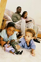 Low angle view of parents sitting on a couch with their son and daughter playing with dolls on the floor