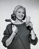 Portrait of a young woman holding a glass of juice and a golf club