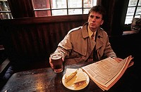 A young businessman reads the Financial Times newspaper over lunch in an english pub