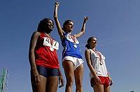Three Female Athletes on Medal Podium