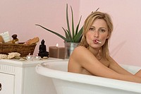 Woman sitting in bathtub, sucking lollipop