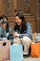 Two young Asian women with shopping bags and cameras sitting in front of a wooden door of a church