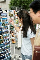 Young Asian woman next to a man grasping a postcard from a rack, selective focus