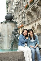 Two young Asian women sitting on the brim of a fountain, focus on foreground