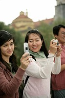 Young Asian woman holding a mobile in her hand whereas an older looking woman is holding a camera, selective focus