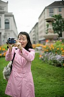 Young Asian woman with a camera standing in front of a park and is laughing, selective focus