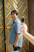 Female hand taking a picture of an Asian man who is standing in front of an ornate door, selective focus