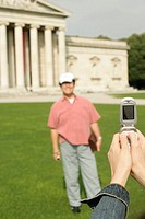 Female hand taking a picture of an Asian man who is standing in front of an antique museum, focus on foreground