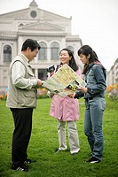 Three Asian people standing in front of a manor on a meadow and are having a look at a map