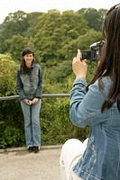 Woman is filming an Asian woman on a bridge, selective focus