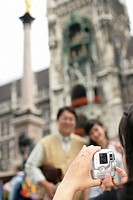 Young Asian woman taking a picture of an Asian heterosexual couple under the golden statue of the Virgin Mother (part of), selective focus