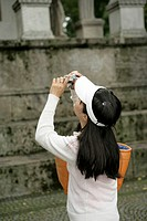 Asian woman with a white cap takinure of an old monument with a digital camera, selective focus