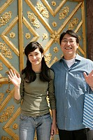 Asian man and woman standing in front of an ornate door