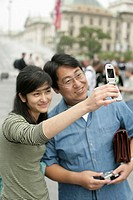 Asian woman is taking a picture of herself and an Asian man, selective focus