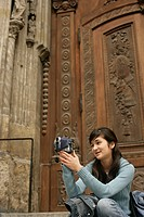 Young Asian woman with a camera in her hand is sitting in front of the wooden door of a church, selective focus