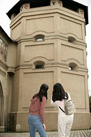 Two Asian women regarding a medieval tower, selective focus