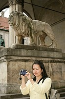 Young Asian woman with a camera standing in front of a the ancient sculpture of a lion, selective focus