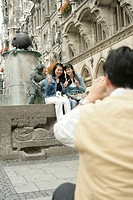 Two young Asian women sitting on the brim of a fountain while a man is taking a picture of them, focus on foreground, selective focus