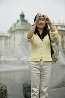 Young Asian woman with a camera standing in front of a fountain on a plaza, selective focus