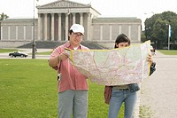 Asian man and woman standing in front of an antique building, both holding a map