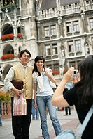 Young Asian woman taking a picture of an Asian man and a woman in front of the town hall of Munich, selective focus