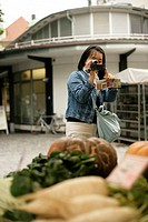 Young Asian woman taking a picture of pumpkins in a sales booth, selective focus