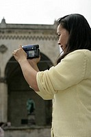 Young Asian woman with a camera standing in front of an ancient building with a sculpture, selective focus