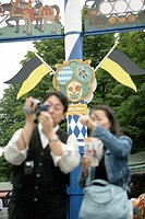 Young Asian woman and man with camera standing in front of a maypole, selective focus